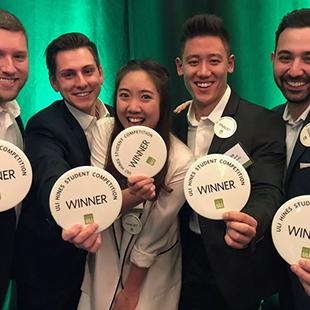 Five students holding buttons that say Winner