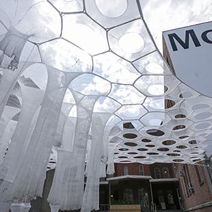 woven white structures creating a canopy in a courtyard