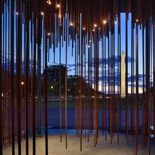 A waterfront scene at dusk viewed through vertical lies of varying lengths.