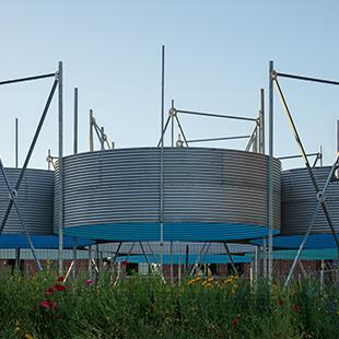 Six circular sections of corrugated metal grain silos grouped together in a field.