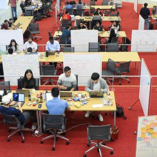 people seated at rows of tables in a large space working on laptops and white boards