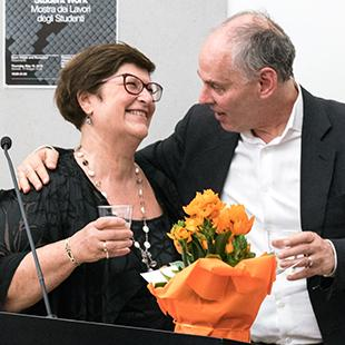 Two people standing behind a microphone in a sidearm embrace with orange flowers