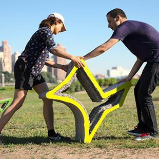 Two people moving a star-shaped, yellow concrete chair on a lawn with two other green chairs and a city skyline in the background
