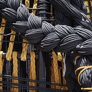 Yellow and black braided rope attached to a black metal frame