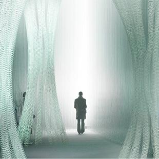 Silhouette of a person walking between translucent fiber columns