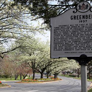 Historic marker sign for Greenbelt, Maryland, with a street behind it and trees in bloom