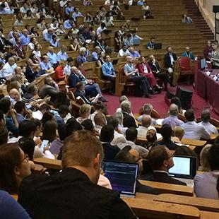 auditorium full of people attending a panel event