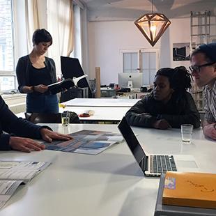 Artist Taiyo Onorato with mfa students at studio table