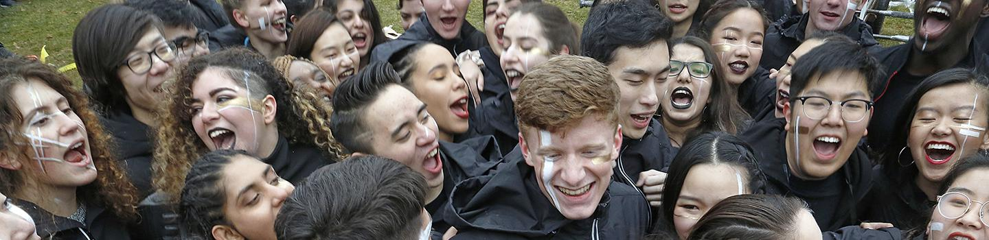 A crowd of young people dressed in black and painted faces, smiling and shouting