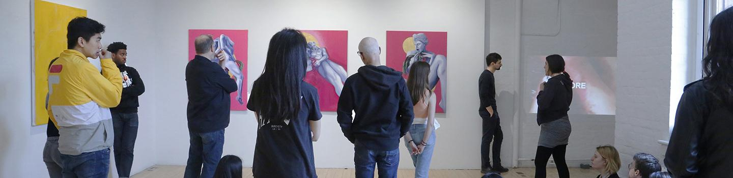 A dozen people stand looking at artwork hanging on the walls of a gallery