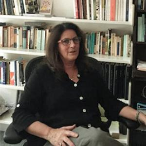 A woman with long, dark brown hair wearing brown rimmed glasses sitting in front of a large bookshelf.