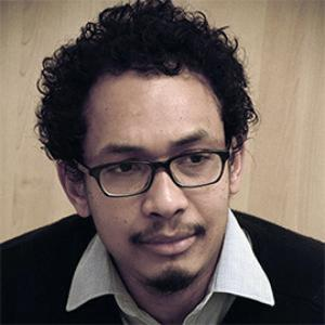 A man with dark curly hair wearing black rimmed glasses.