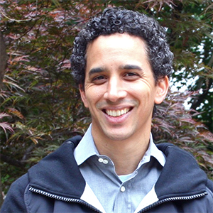 smiling man with dark, curly hair