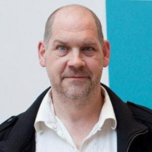 headshot of a man wearing a black jacket and white shirt in front of a turquoise and white wall