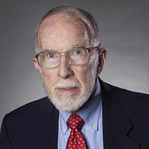 man with gray hair and beard wearing glasses and a dark suit jacket, blue shirt and red tie