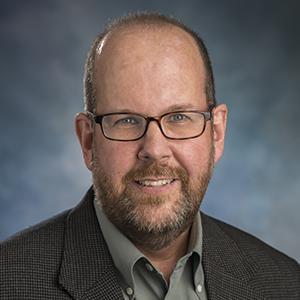 headshot of a man wearing glasses