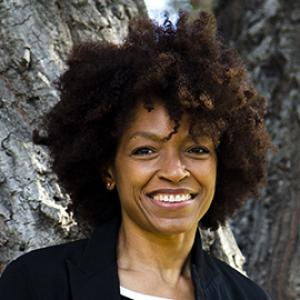 A smiling woman with a brown afro, who is wearing a black blazer.