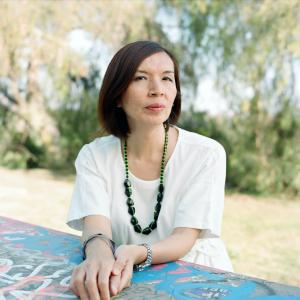 A woman in a white blouse and a green necklace, with trees in the background