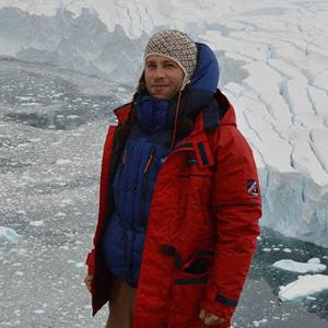 photo of a man in red and blue winter coat on glacier