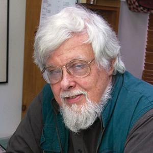 Portrait of a man with white hair and a white beard, wearing large wire rimmed glasses and a turquoise and grey long sleeve shirt.
