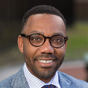 Photo headshot of a person with glasses and suit with a blurred outdoor background.