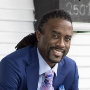 Man with dark braids tied back, dark facial hair, blue suite