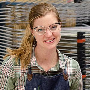 woman in glasses and a plaid shirt in front of flat racks with art works in them