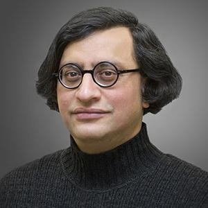 headshot of man with black hair and glasses