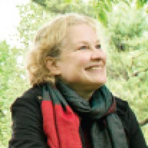 a woman smiling wearing a scarf