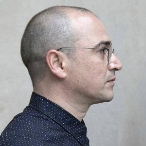Portrait of the profile of a man wearing a navy blue button up shirt, and wire rimmed glasses.