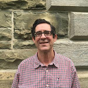 headshot of a man in a plaid shirt standing in front of a brick wall