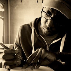 sepia tone photo of a man in a hat and glasses writing