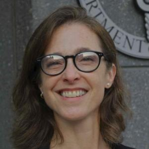 person smiling with glasses in front of a grey background