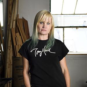 Woman with blonde hair and bangs wearing a black shirt in front of wood pieces and a window.