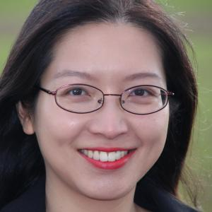 A woman smiling and wearing glasses