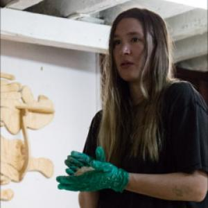Image of woman with long hair, green gloves, dark shirt holding something in her hand.