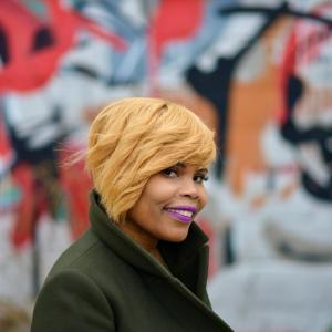 A person with short blonde hair and purple lipstick wearing a green coat standing in front of a multicolored art wall.