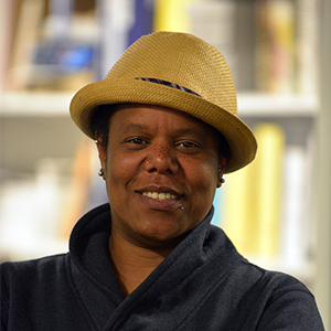 headshot of woman with yellow hat with bookshelf background
