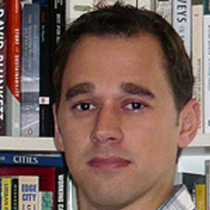 headshot of man with bookshelf in background