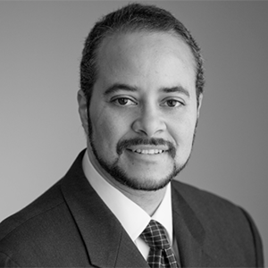 black and white photo of a man with facial hair in a suit