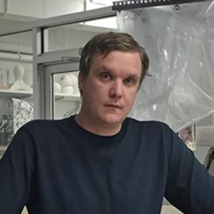 A man with short blonde hair wearing a black shirt.