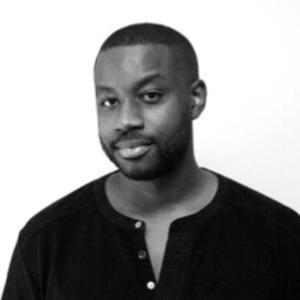 black and white photo of a man with short hair short facial hair and dark shirt