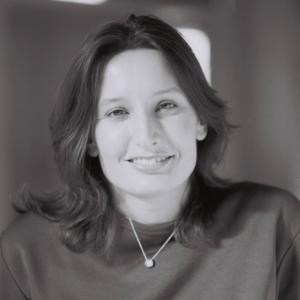A black and white photo of a smiling woman's face