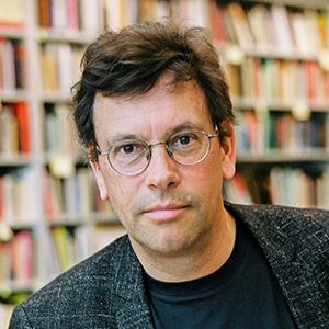 Portrait of a man with short brown hair and rounded glasses, posed in front of a library bookshelf