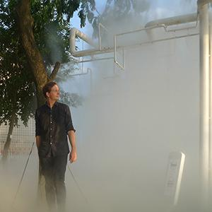 a man standing in fog or smoke under a tree