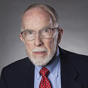 headshot of a man with a white beard, glasses, and a suit