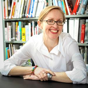 Portrait of a woman wearing a white button down shirt, black rectangular glasses and blond hair. The woman's hands are rested on a black table, with the portrait taken in front of a book case.