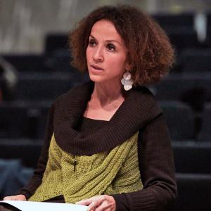 woman with curly hair, large earring, wearing green and brown sweater