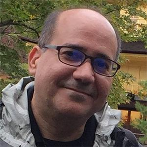 A smiling, bald man with glasses in a leafy background.