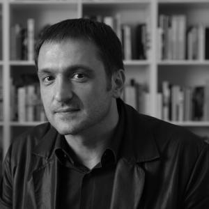 black and white photo of a man with bookshelves in the background